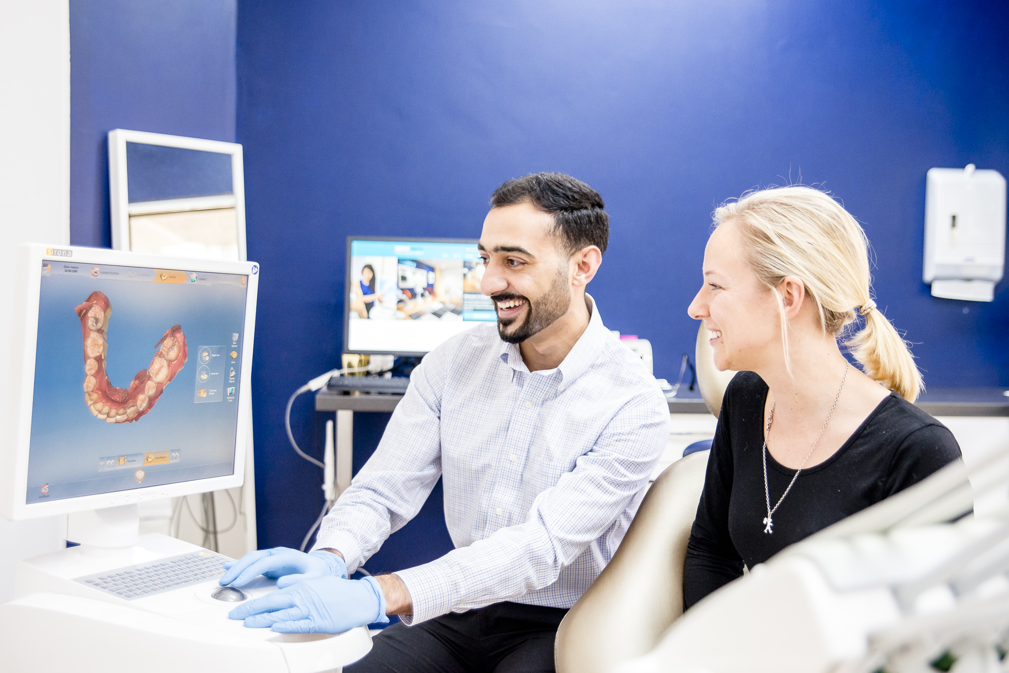 Dentist at Simply Teeth explaining tooth problem on a computer