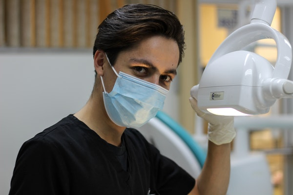 dentist with mask holding dental lamp