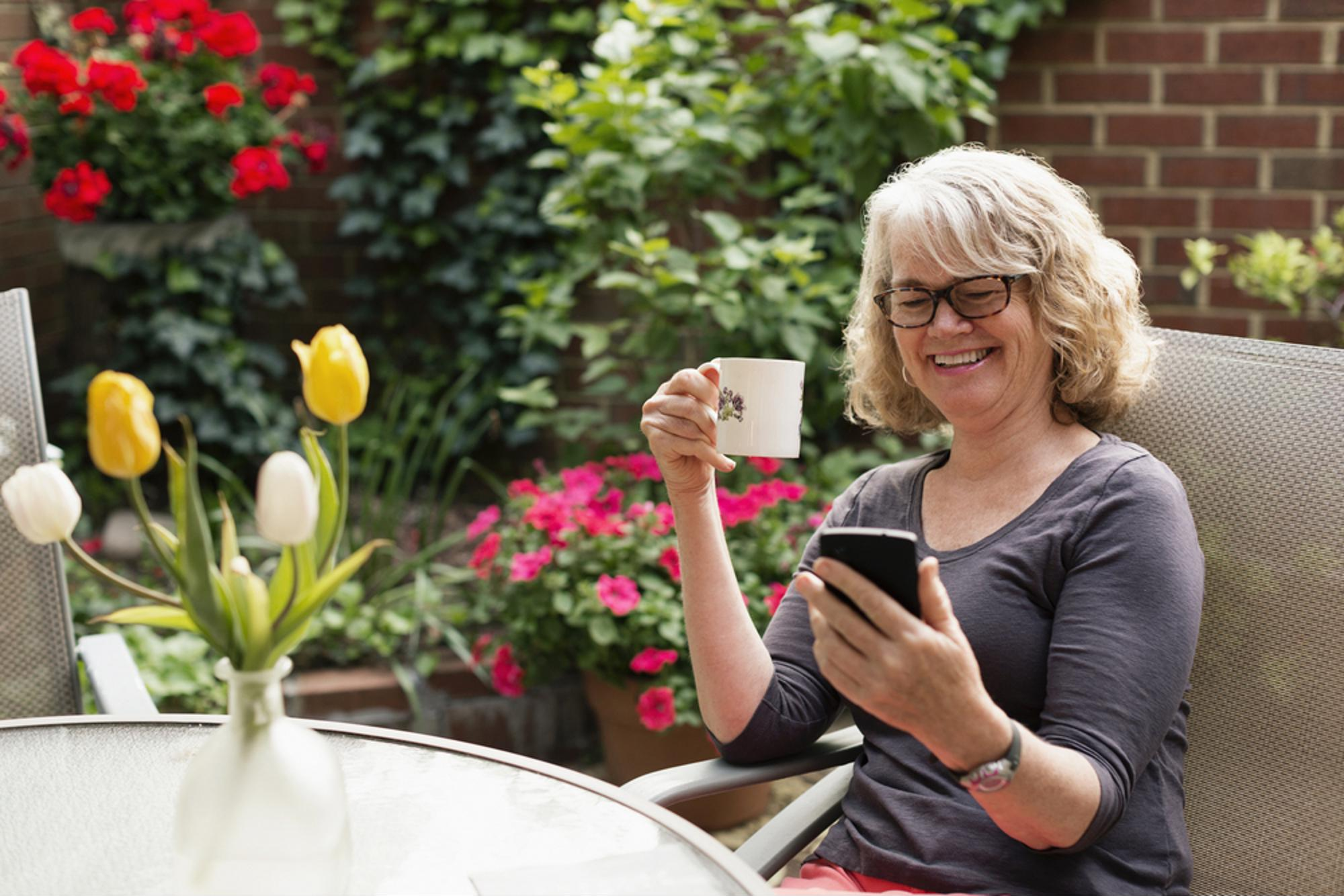 A lady drinking coffee and using her phone